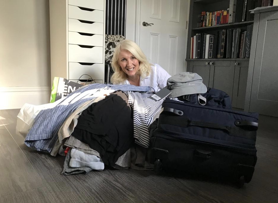 Jayne surrounded by a pile of clothes that she is trying to get into her smallish suitcase